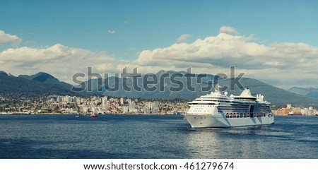 Cruise ship and city skyline with mountains and urban buildings in Vancouver, Canada.