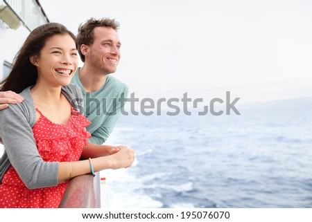 Cruise ship couple romantic on boat looking at view in romance. Happy lovers, woman and man traveling on vacation travel sailing on open sea ocean. Young Asian woman and Caucasian man. - stock photo