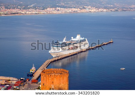 Cruise ship in Alanya harbor from Alanya peninsula - stock photo