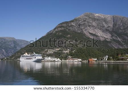 Cruise ship in Eidfjord town (Hardangerfjord, Norway) - stock photo