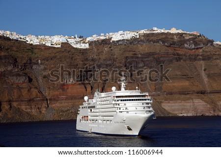 Cruise ship in the beautiful Greek island Santorini, Greece. - stock photo