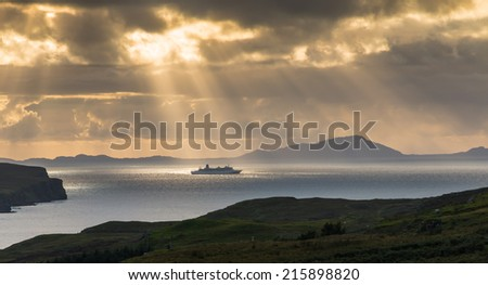 Cruise ship passing in front of the Isle of Skye, Scotland, under a dramatic evening sky with sunbeams hitting the vessel - stock photo