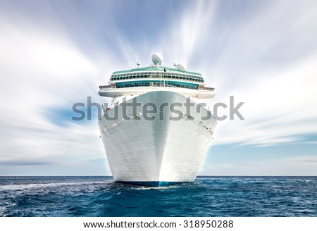 Cruise ship sailing in ocean, white liner on blue sea with blurred sky - stock photo
