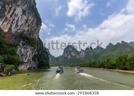 Cruise ship travels the magnificent scenic route along the Li river from Guilin to Yangshou. - stock photo