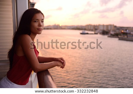 Cruise ship vacation woman enjoying balcony at sea with beautiful sunset on travel at sea. Relaxed woman enjoying private balcony in stateroom. Asian Chinese / Caucasian woman in dress on cruise liner - stock photo