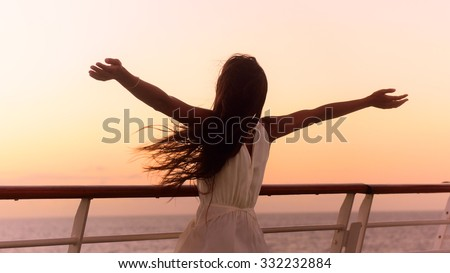 Cruise ship vacation woman enjoying sunset on travel at sea. Free happy woman looking at ocean in happy freedom pose with arms out. Woman in dress on luxury cruise liner boat. - stock photo
