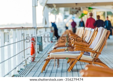 Cruise Ship Wooden Deck Chairs and Some Senior Tourists.  - stock photo