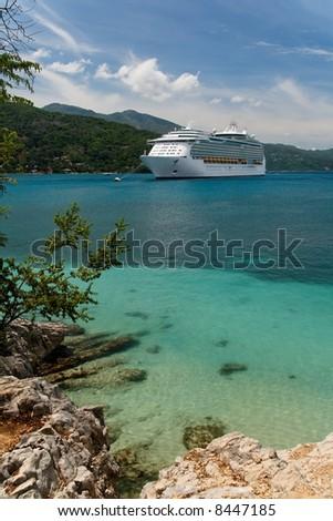 Cruiseship anchoring in a caribbean bay - stock photo