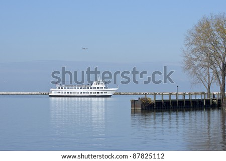 Cruising the Harbor:  A tourist excursion boat cruises inside the breakwater separating the western basin of the harbor at Cleveland, Ohio from the open waters of Lake Erie - stock photo