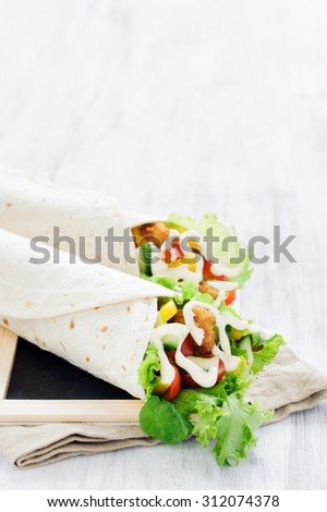 Crumbed chicken tortilla wrap with fresh healthy green salad, tomatoes, cucumber and bell peppers - stock photo