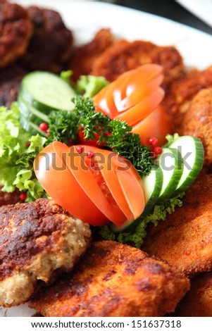 Crumbed fried meat and fish on a buffet table at a catered event with fresh salad ingredients as a garnish - stock photo