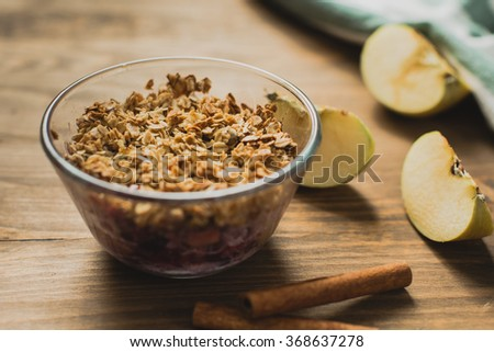 Crumble Dessert with apple, oat flakes, cinnamon and berries in glass bowl, close up - stock photo