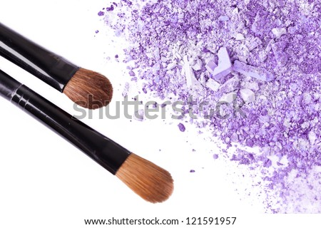 Crumbled eyeshadow with brush, closeup on white