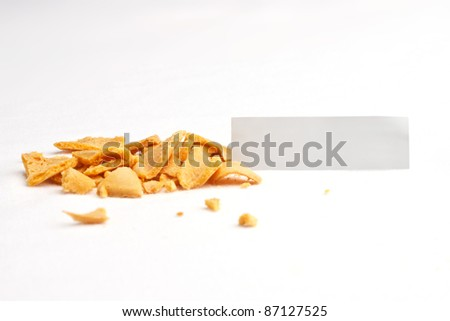 Crumbled fortune cookie with blank off-white slip against white background