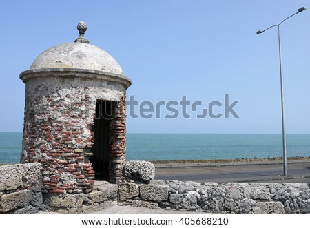 Crumbling Brick Look Out Tower on Fort Wall Surrounding Historical Area of Cartagena Overlooking Caribbean Sea in Colombia - stock photo