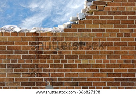 crumbling brick wall with white wispy clouds in blue sky - stock photo