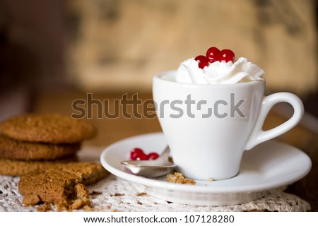 Crumbling oat cookies biscuits with hot coffee and whipped cream with cranberries on top. Shallow DOF - stock photo