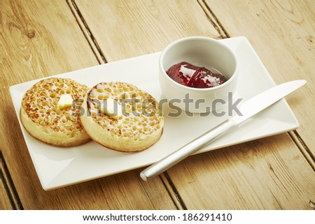 Crumpets toasted on white dish and wooden table top - stock photo
