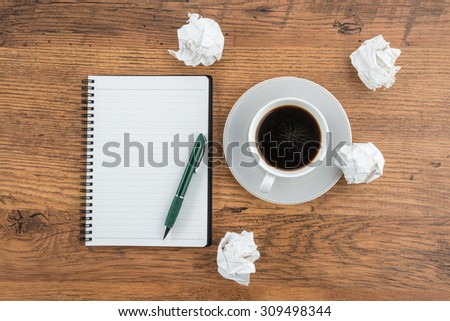 crumple paper, notebook and pen with cup of coffee on the desk - stock photo