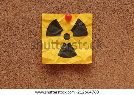 Crumpled adhesive note with Radioactive Sign on corkboard (bulletin board).