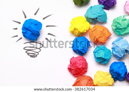 Crumpled blue paper light bulb over white background. - stock photo