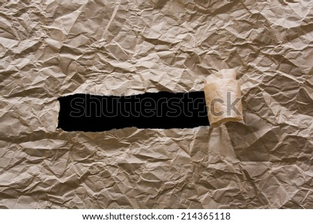 Crumpled brown paper torn in the middle on a black background - stock photo