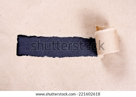 Crumpled brown paper torn in the middle on a black background. - stock photo