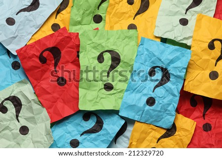 Crumpled colorful paper notes with question marks. - stock photo