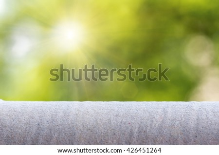 crumpled gray paper on the background of the solar green bokeh - stock photo