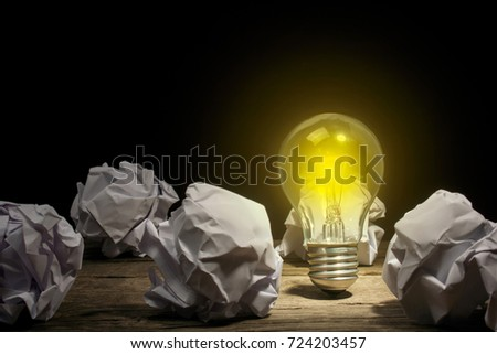Crumpled office paper in a ball and a glowing light bulb on a black background. A new concept idea. Copy space for text