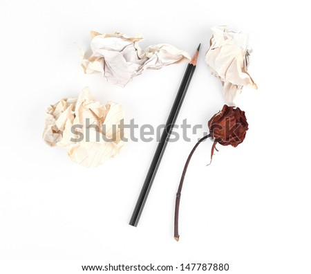 Crumpled old papers and pencil with wilting rose on white background - stock photo
