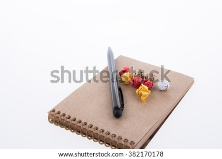 Crumpled paper and ballpoint pen on a spiral notebook on white background - stock photo