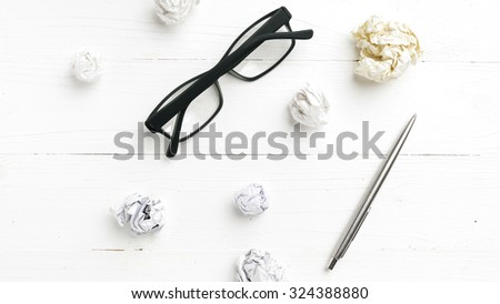crumpled paper and eyeglasses with pen over white table - stock photo