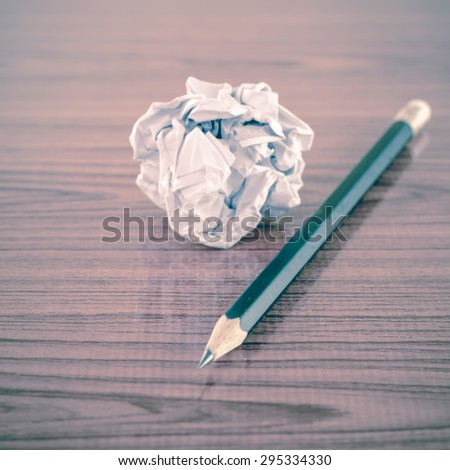 crumpled paper and pencil on wood background - stock photo