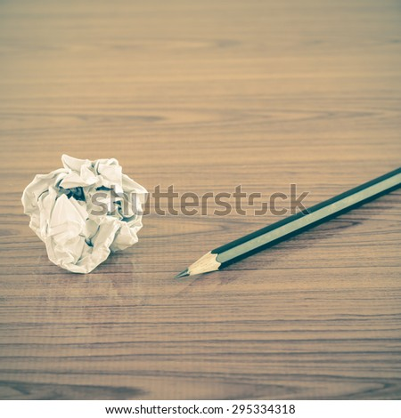 crumpled paper and pencil on wood background vintage style - stock photo