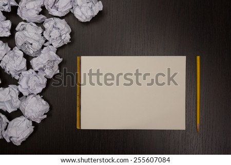 Crumpled paper balls and blank sheet of paper with pencil on black background. Paper wad. Creativity problems. Searching ideas. - stock photo