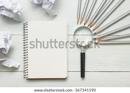 crumpled paper balls, magnifying glass, pencils and notebook with blank white sheet  on wooden table. Creativity crisis concept - stock photo