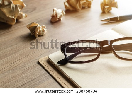 Crumpled paper balls with eye glasses and notebook on wood desk with soft light - stock photo