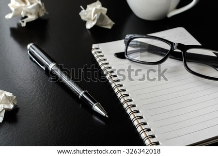 Crumpled paper balls with eye glasses, pen and notebook, Monochrome tone - stock photo