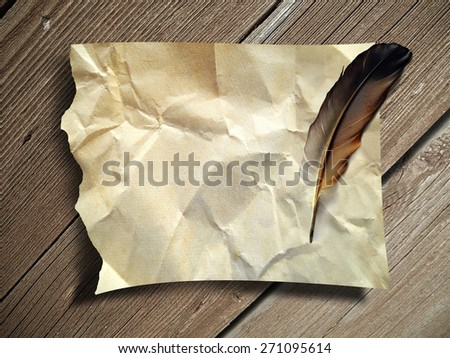 Crumpled paper for text with feather on wood background - stock photo