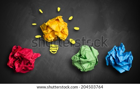 crumpled paper in different colors and one as an idea - stock photo