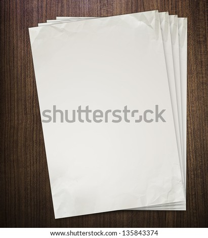 Crumpled paper on old wood texture - stock photo