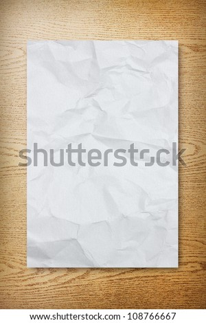 Crumpled paper on wood background