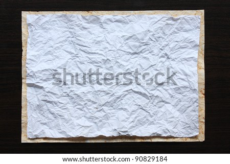Crumpled paper on wood background.