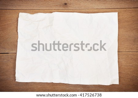Crumpled paper sheet on a wooden background