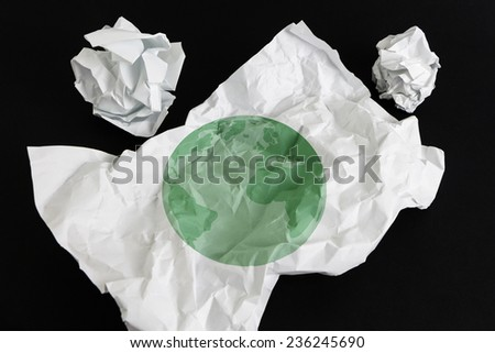 Crumpled paper sheet with Earth illustrated on it, isolated - stock photo