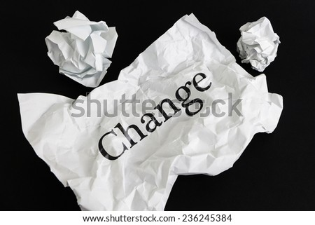 Crumpled paper sheet with word Change isolated on black - stock photo