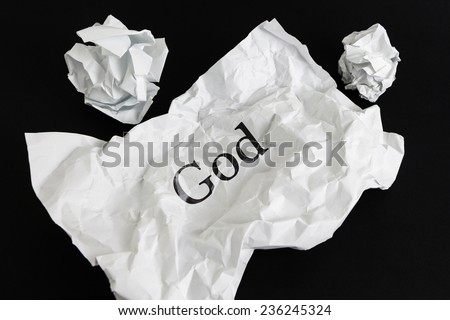 Crumpled paper sheet with word God isolated on black - stock photo