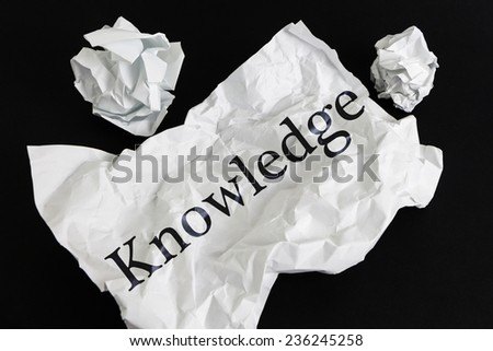 Crumpled paper sheet with word Knowledge isolated on black - stock photo