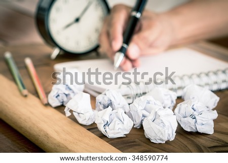 Crumpled papers with hand hold the pen as a background , selective focus on crumpled papers - stock photo